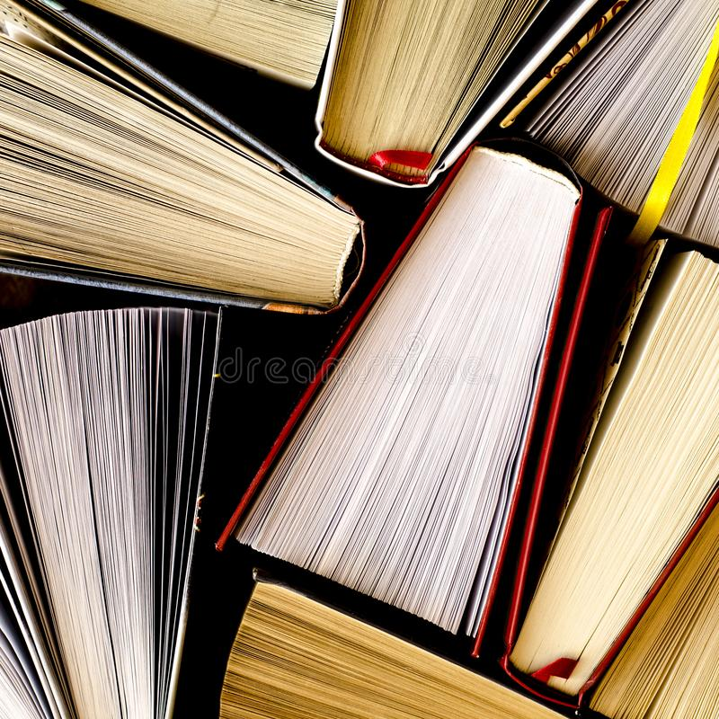 Lots of colourful thick open books stand on a dark background. Ready to read paper shop bookshelf bookstore cardboard education fiction folder information stock photos