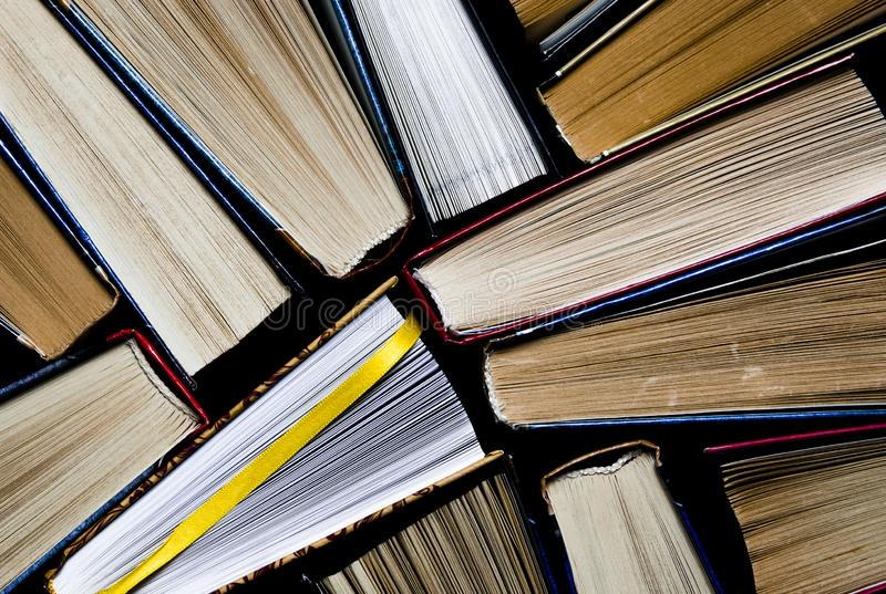 Lots of colourful thick open books stand on a dark background. ready to read royalty free stock photos