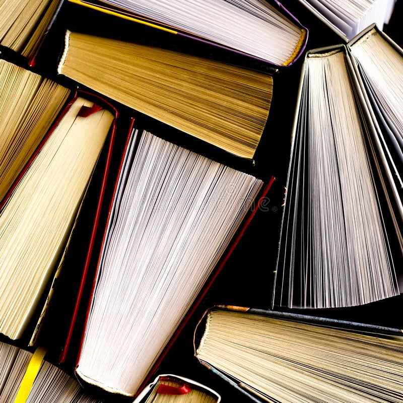 Lots of colourful thick open books stand on a dark background royalty free stock photography