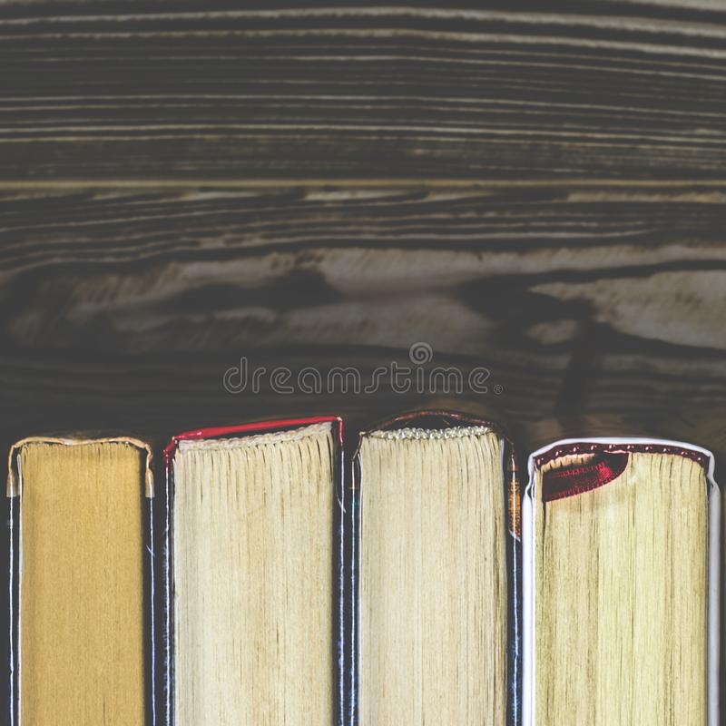 Lots of colourful thick open books stand on a dark background royalty free stock photos