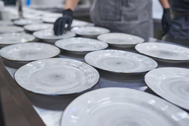 Lots of empty plates on the table. Many empty plates on a table in a restaurant kitchen stand one after another stock photo