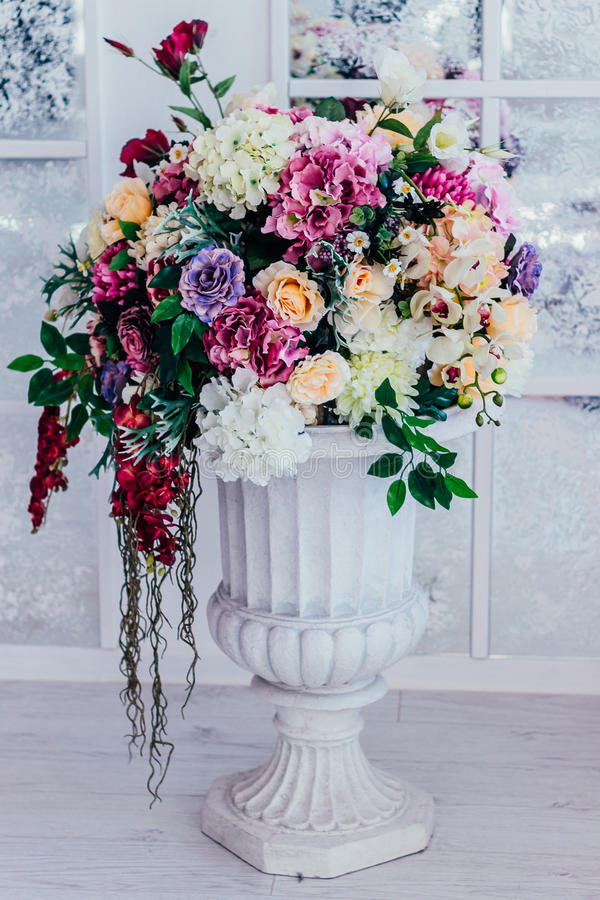 Lots of flowers in a white pot on a stem on a white for A lot of different flowers make a bouquet