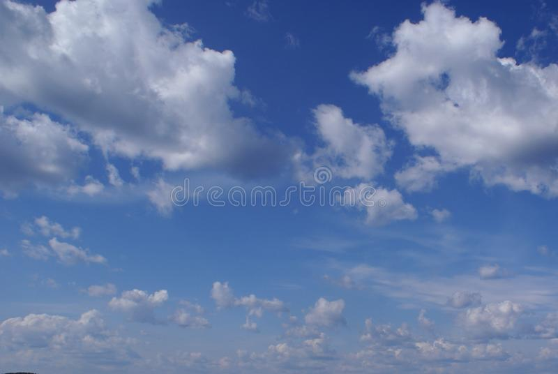 Lots of fluffy white clouds in the blue sky. royalty free stock images