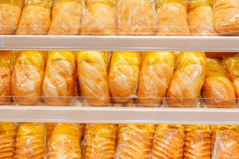 Lots of fresh loaves of bread on shelves royalty free stock images