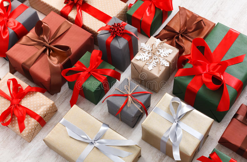 Lots of Gift boxes background, christmas presents in paper. Lots of Gift boxes on white background. Presents in craft and colored paper decorated with red satin royalty free stock photography