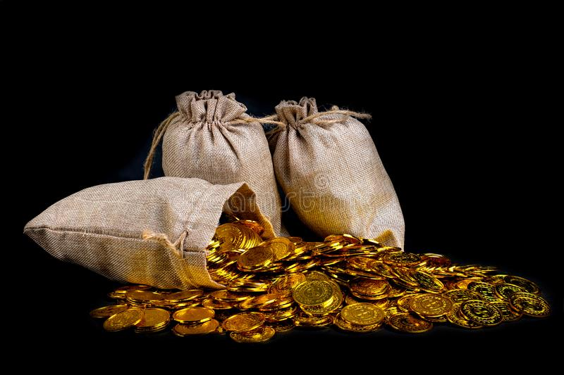 Stack gold coin in treasure sack. Lots of gold coin in treasure sack at black background royalty free stock image