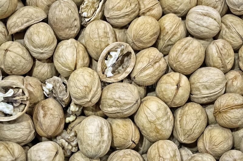 Lots of inshell walnuts on the market counter. Lots of inshell walnuts on the counter on the walnut market texture royalty free stock images