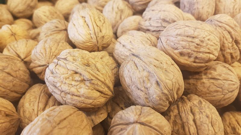 Lots of inshell walnuts texture. Photo about lots of brown inshell walnuts texture background in a market stock images
