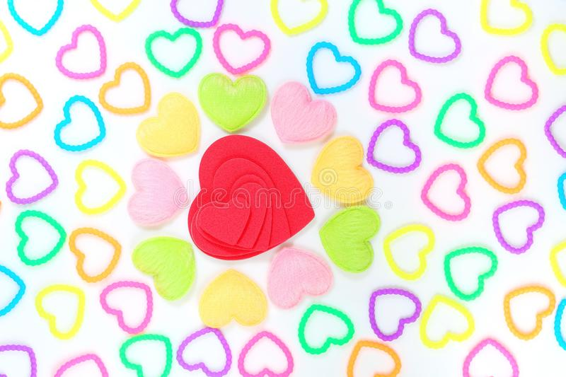 Lots of love. Small colourful hearts align towards a bigger red heart object isolated on white back ground . Concept of love and attraction royalty free stock photos