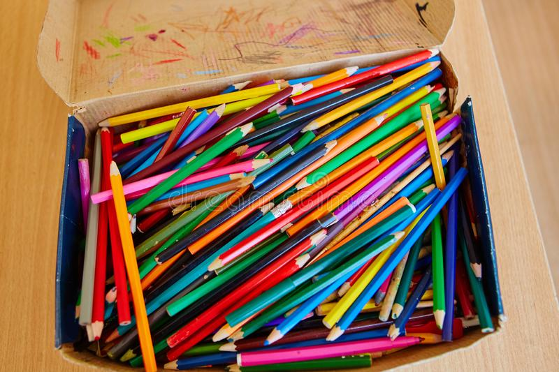 Lots of old colored wooden pencils in a cardboard box with children`s doodles royalty free stock photography