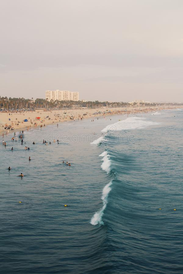 Lots of people on beach. While a wave is breaking. photo taken in Santa Monica California from onto of the pier stock photo