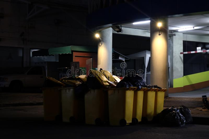 Lots of Recycled plastic bins yellow in the night dark at urban Bangkok Thailand, Bin for waste garbage, Many Bins on floor stock photography