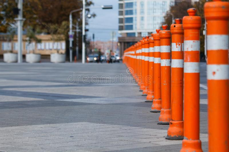Lots of road orange pillars. Paving slabs in the area near the road. City Scene stock photo