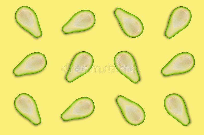 Lots of scattered tasty fresh halves of organic avocado on yellow table in kitchen or market. Top view. Cooking concept stock photography
