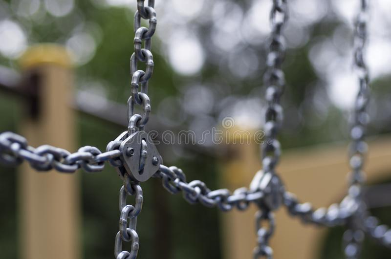 Lots of shiny chain links diagonal and transverse. On the background beautiful bokeh stock photography