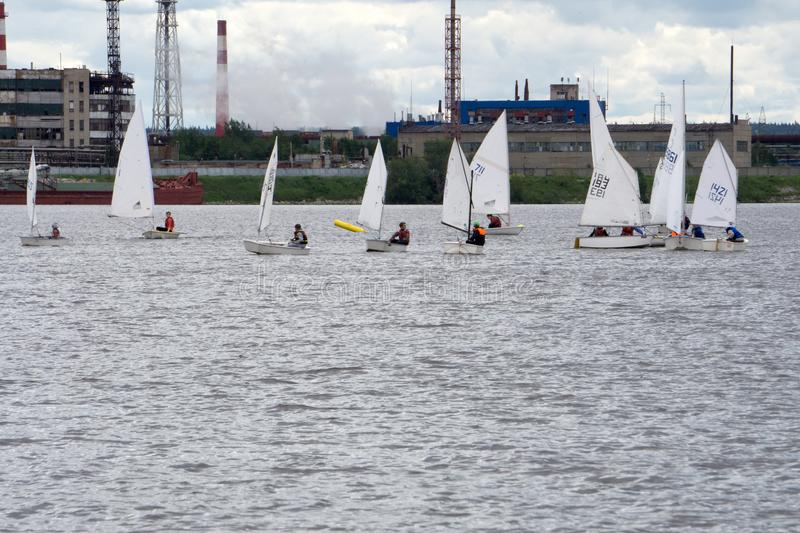 Lots of Small white boats sailing on the lake . stock photo