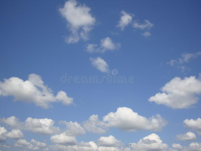 Lots of small white clouds on blue sky background royalty free stock photography