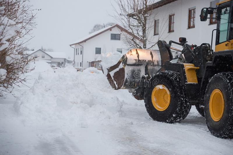 Lots of snow on the street. tractor clears the snow with the loader royalty free stock photo