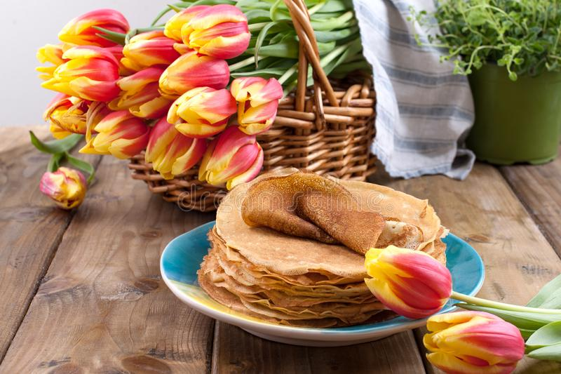 Lots of thin pancakes on a wooden background or table, and a basket with fresh red-yellow tulips. Baking is home for the royalty free stock image