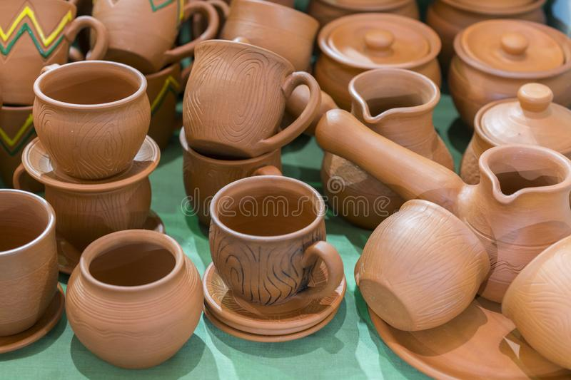 Lots of traditional ukrainian handmade clay pottery production. brown pottery. Clay plates and cups.  royalty free stock photo