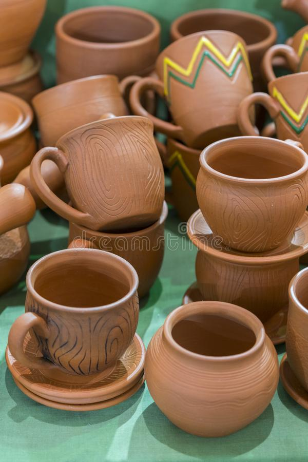 Lots of traditional ukrainian handmade clay pottery production. brown pottery. Clay plates and cups. vertical photo.  stock photos