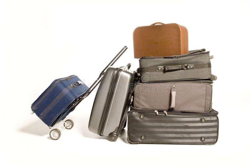 Lots of Travelling Suitcases. Big family's worth of various piled up travelling suitcases isolated on white stock image