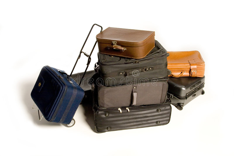 Lots of Travelling Suitcases. Big family's worth of various piled up travelling suitcases isolated on white royalty free stock photo