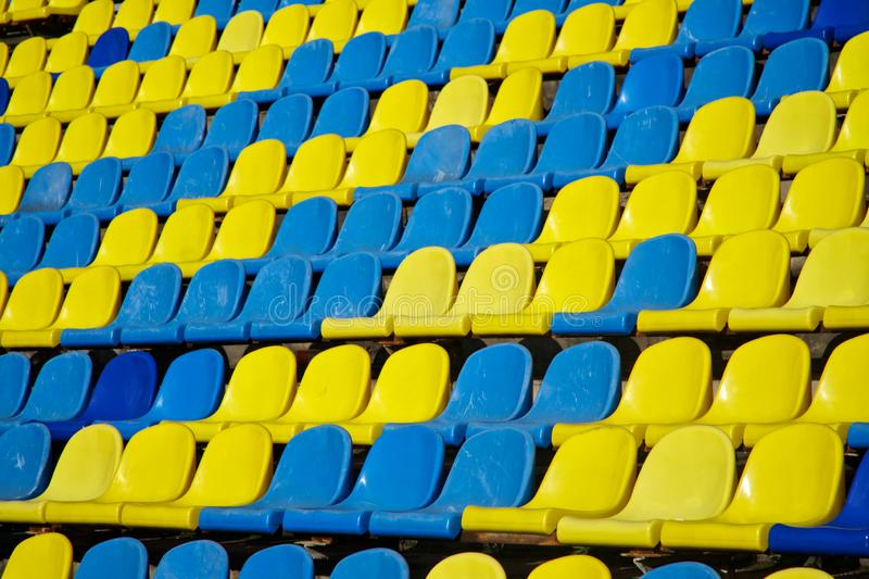 Lots of used blue and yellow plastic seats in an open stadium. Free access. Empty seats, without spectators. Waiting for the sight stock image