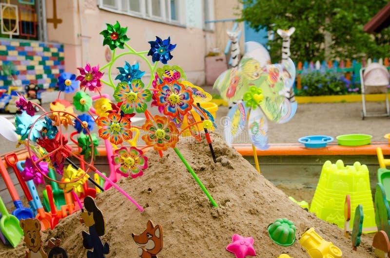 Lott av barns mång--färgade skyfflar med hinken i sandlåda på lekplatsen i sommardag royaltyfria bilder