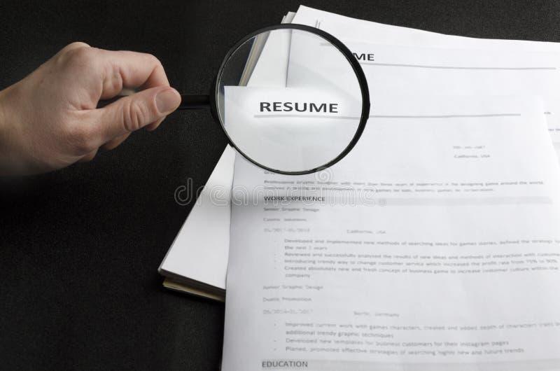Lott av meritförteckningapplikationer på det svarta skrivbordet, timme-innehavförstoringsglas, begrepp av sökande av yrkesmässiga fotografering för bildbyråer