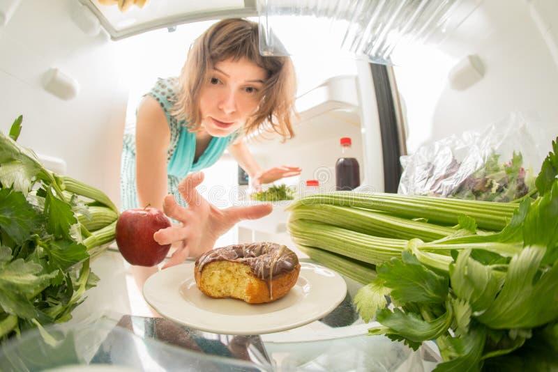 Lotta di dieta: Una mano che afferra una ciambella dal frigorifero aperto in pieno dei verdi immagine stock libera da diritti