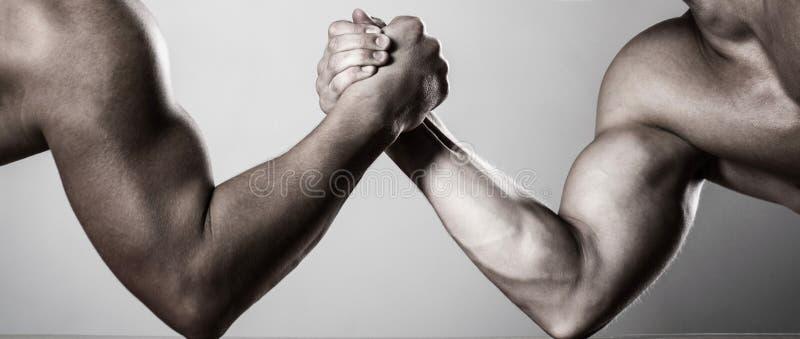 Lottare di braccio dei due uomini Rivalità, primo piano del braccio di ferro maschio Due mani Uomini che misurano le forze, armi  fotografie stock