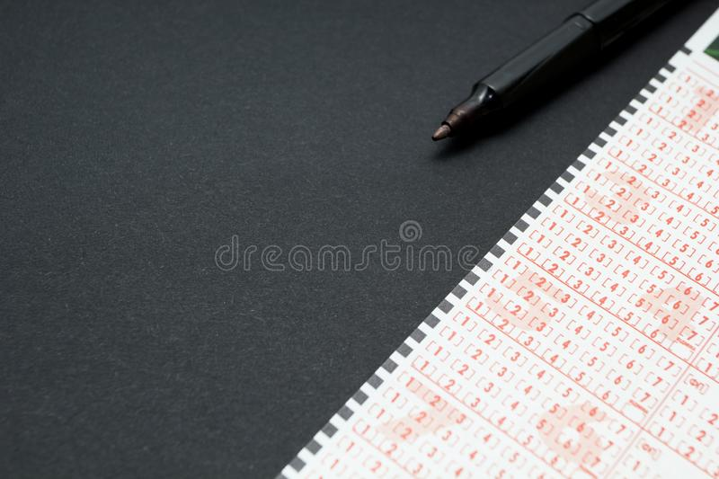 Lottery ticket with pen, person marking number. Black background, space for text royalty free stock photography