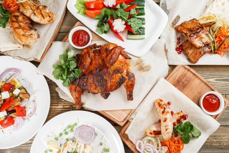 Lotti arrostiti di alimento Servendo su un bordo di legno su una tavola rustica Menu del ristorante con barbecue, una serie di fo immagine stock