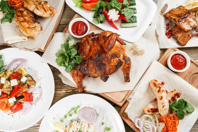 Lotti arrostiti di alimento Servendo su un bordo di legno su una tavola rustica Menu del ristorante con barbecue, una serie di fo immagine stock libera da diritti