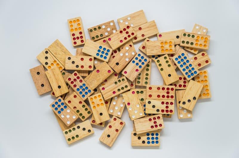 Lotti dei domino di legno su fondo bianco con il fuoco selettivo immagini stock libere da diritti