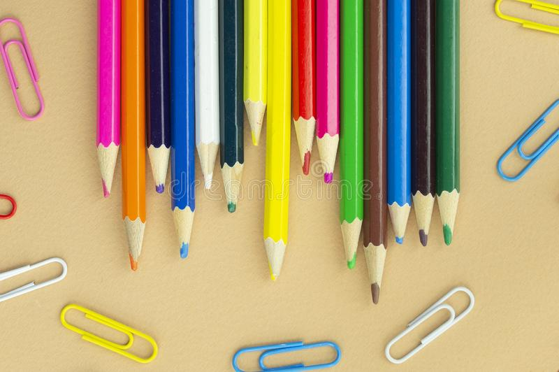 Lotti delle matite variopinte e delle graffette su un fondo beige piacevole fotografia stock libera da diritti