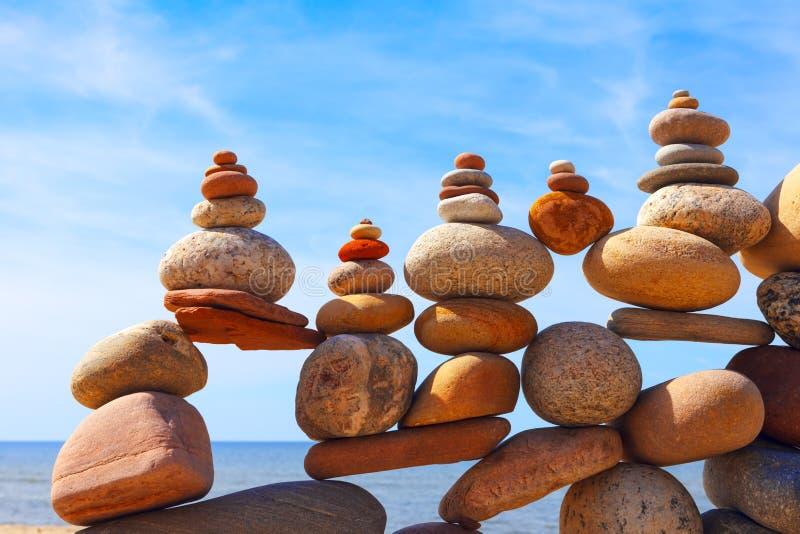 Lotti delle pietre equilibrate e variopinte su una spiaggia sui precedenti del mare fotografia stock