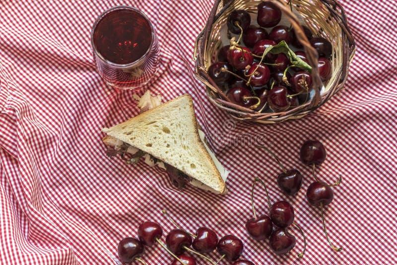 Lotti delle visciole e di un panino del pane del pane tostato su una coperta di picnic del plaid, fotografia di natura morta immagini stock libere da diritti