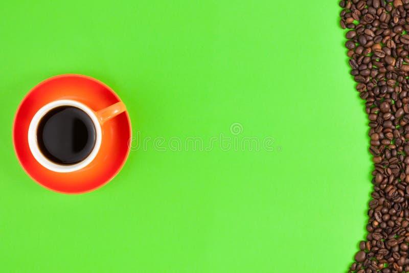 Lotto dei chicchi di caffè arrostiti presentato nell'onda della forma su Libro Verde accanto alla tazza ceramica piena di caffè n fotografia stock libera da diritti