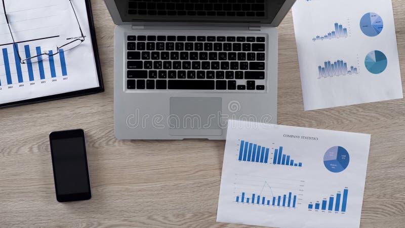 Lotto dei grafici per analizzare menzogne sullo scrittorio nell'ufficio dell'uomo d'affari, vista superiore immagine stock