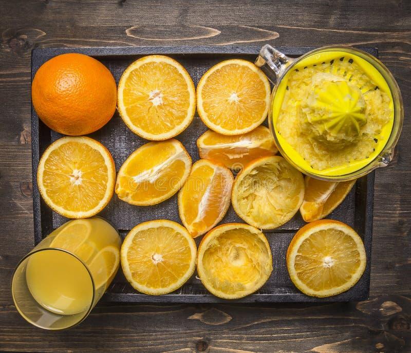 Lotto delle arance con gli spremiagrumi e un vetro di succo in una fine rustica di legno di vista superiore del fondo del vassoio fotografia stock