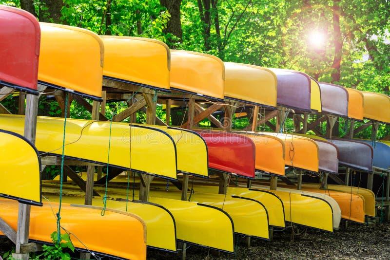 Lotto di multi kajak colorati sulla banca del fiume, di estate o di tempo di molla Canoe variopinte o barche di kayak parcheggiat immagine stock libera da diritti