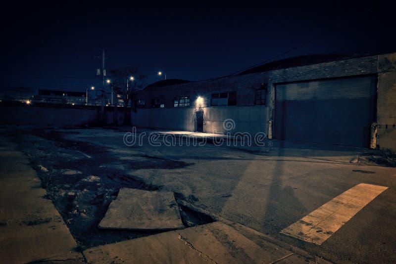 Lotto vuoto spaventoso scuro alla notte con la porta ed il magazzino gated fotografia stock