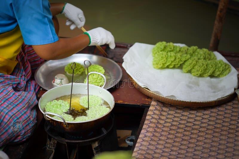 Lotus Blossom Cookie Kanom Dok curruscante Jok frió con aceite en una cacerola imagenes de archivo