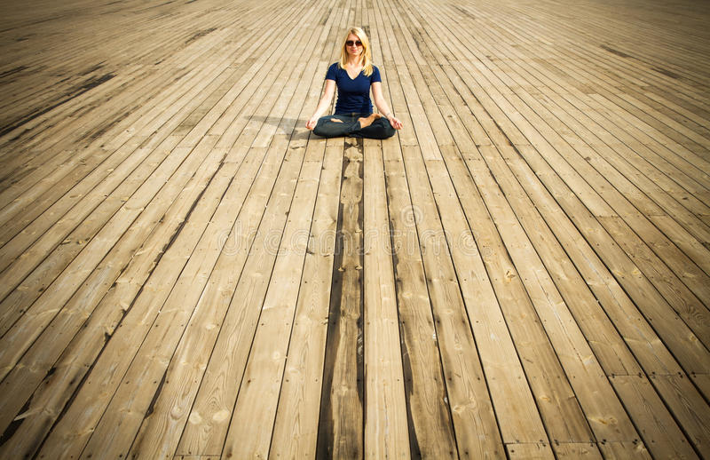 Lotus position. Young woman meditating sitting in lotus position on wooden floor royalty free stock photo