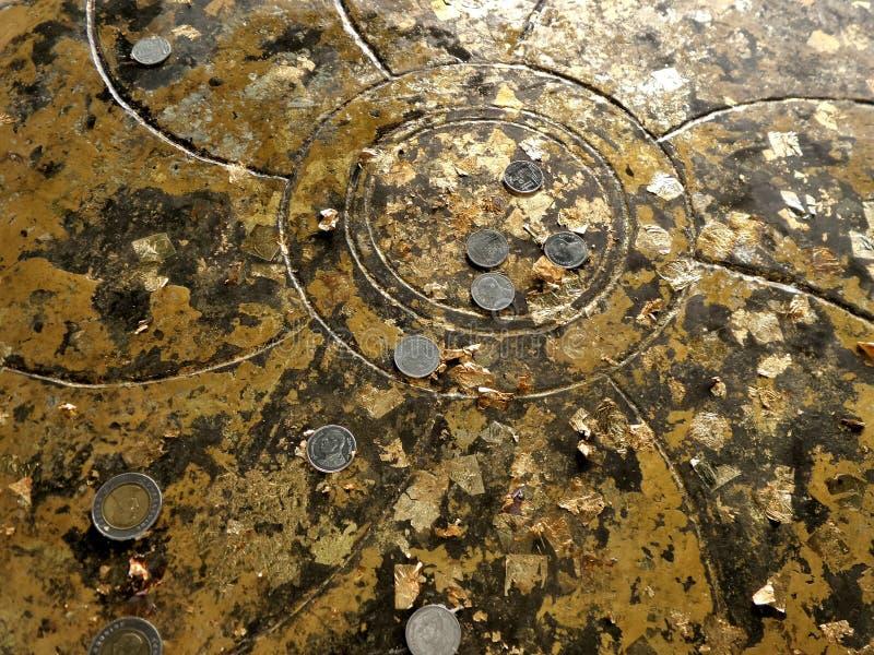 Lotus que talla en la cubierta de descanso de los lenguados de Buda con las hojas y la moneda del oro fotografía de archivo