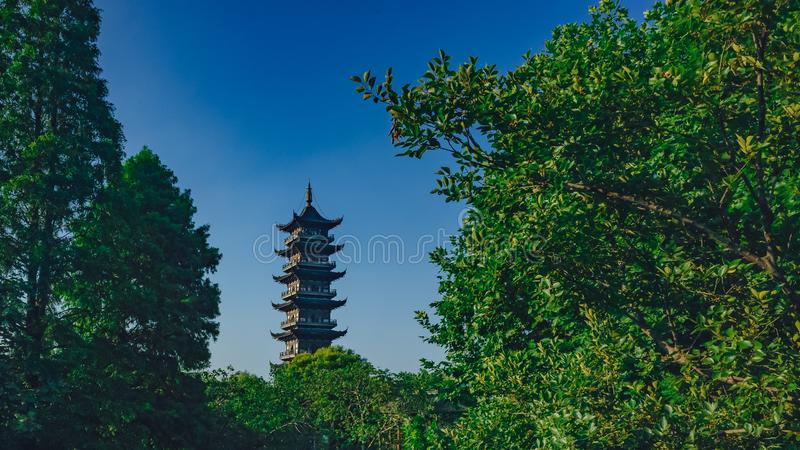 Lotus Tower between trees under blue sky in the old town of Wuzhen, China. View of Lotus Tower between trees under blue sky in the old town of Wuzhen, China stock images