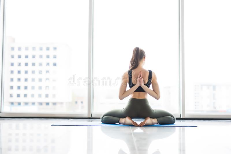 Lotus Yoga hermosa joven que presenta en ventanas panorámicas en fondo de la ciudad fotografía de archivo