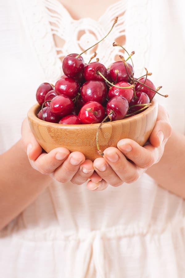 Louça com as cerejas nas mãos da mulher imagem de stock royalty free